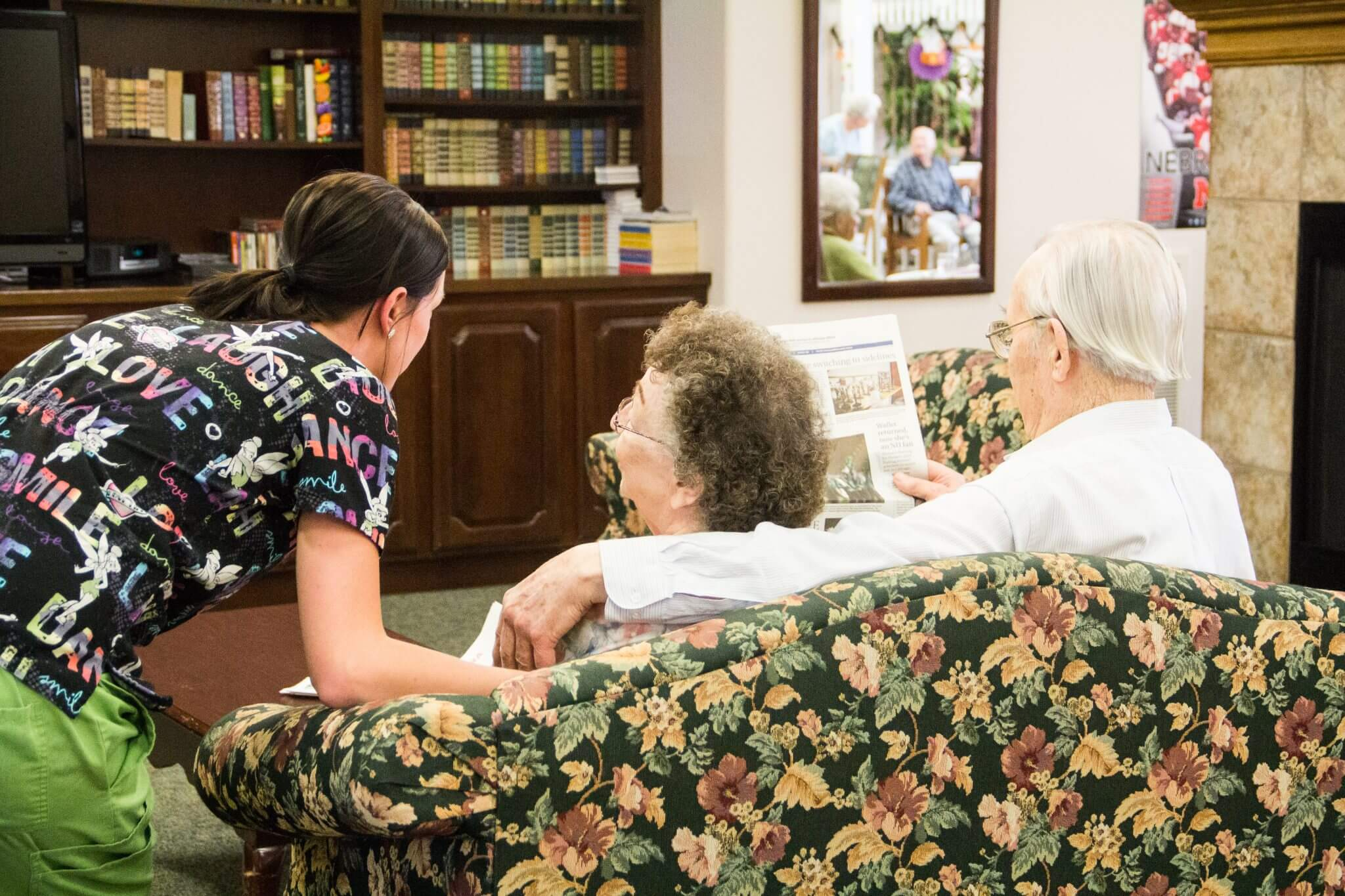 elderly couple sitting on floral couch chatting with nurse