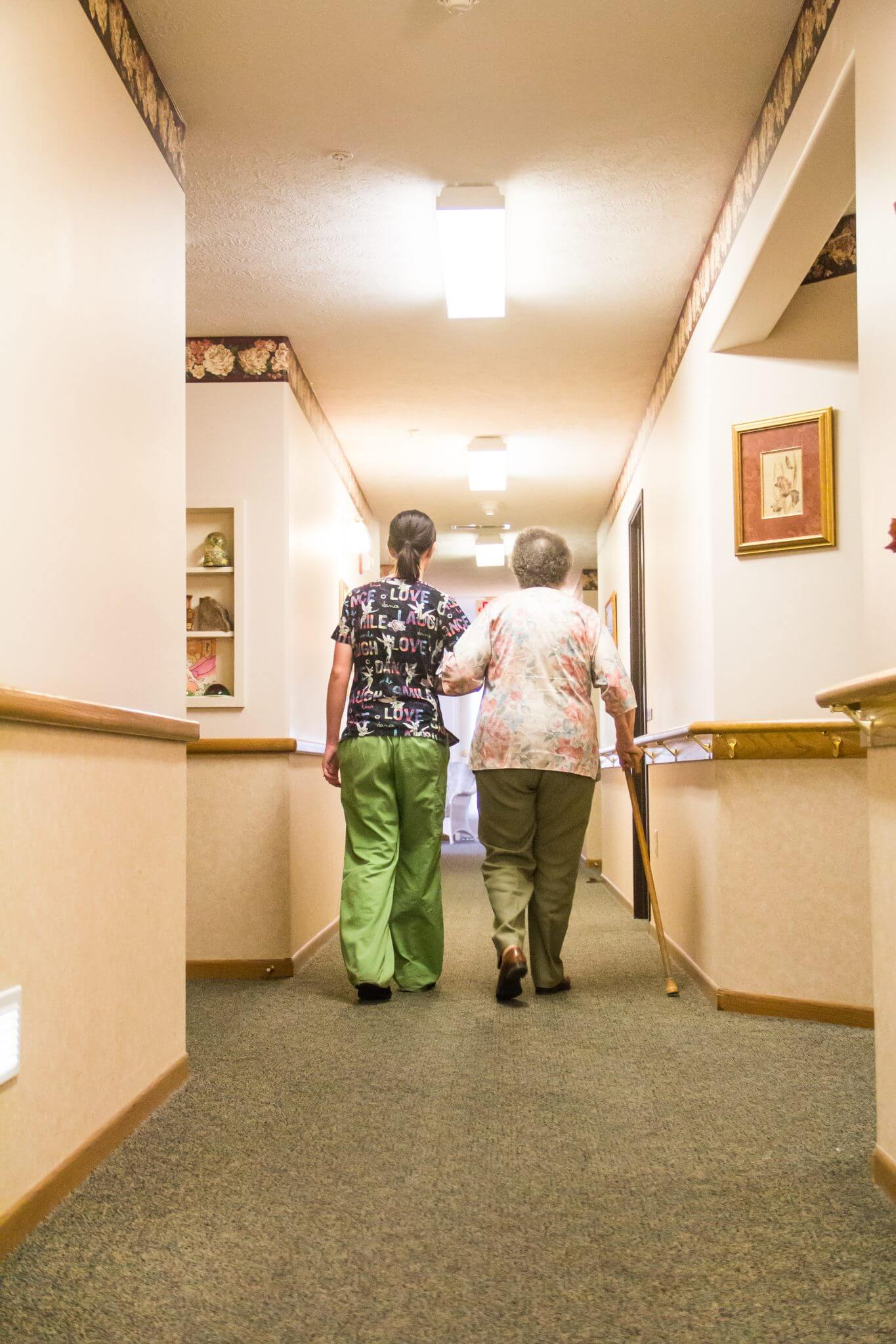 elderly woman and nurse walking down hallway