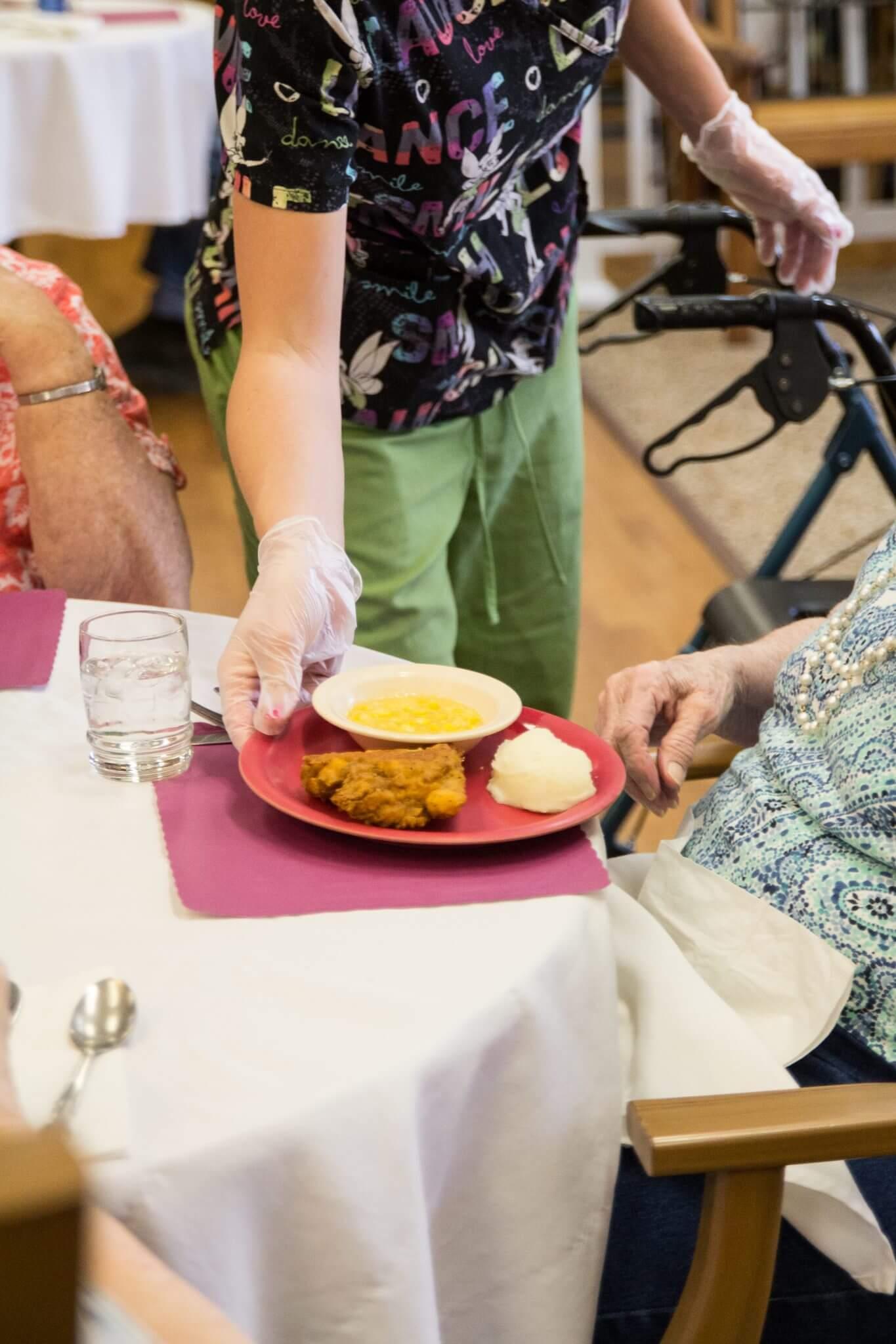 nurse serving a resident dinner