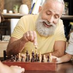 assisted living resident playing chess with grand children during a visit