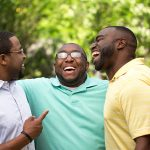 group of three african american men hugging and laughing