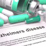 """close-up of pills, and needle on a piece of paper that says """"Alzheimer's disease"""""""