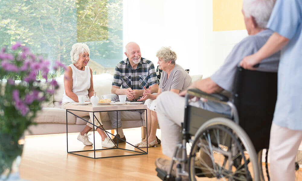 elderly people sitting around coffee table talking