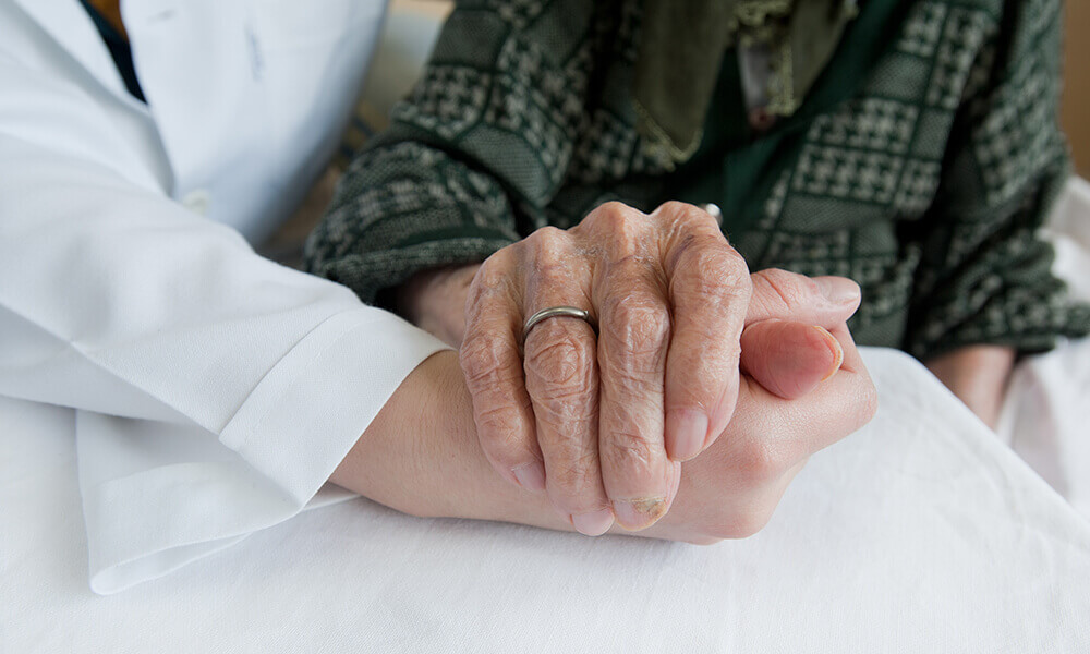 elderly person's hand holding doctor's hand