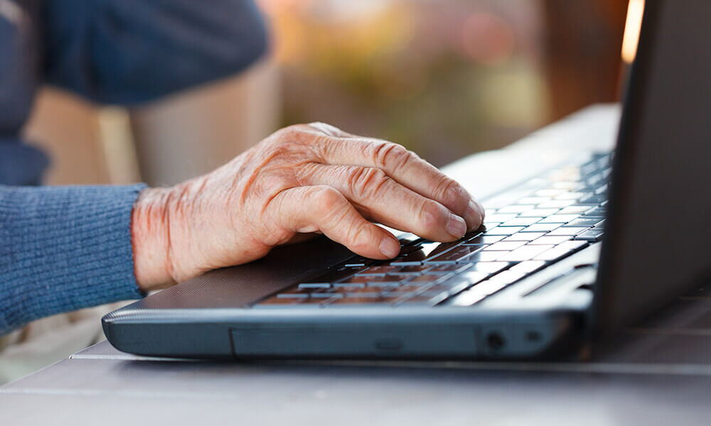 elderly man working on laptop