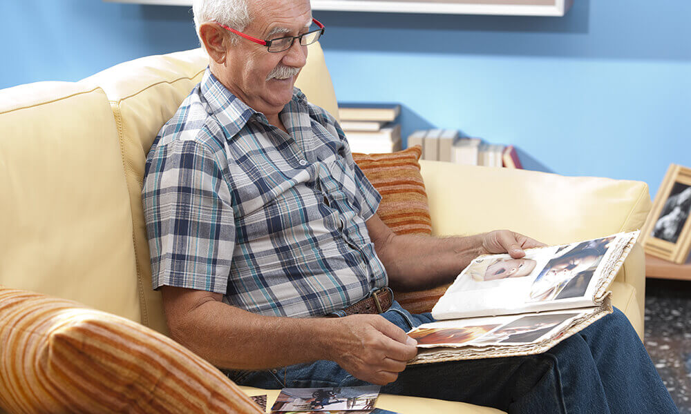 elderly man sitting on couch looking at family pictures