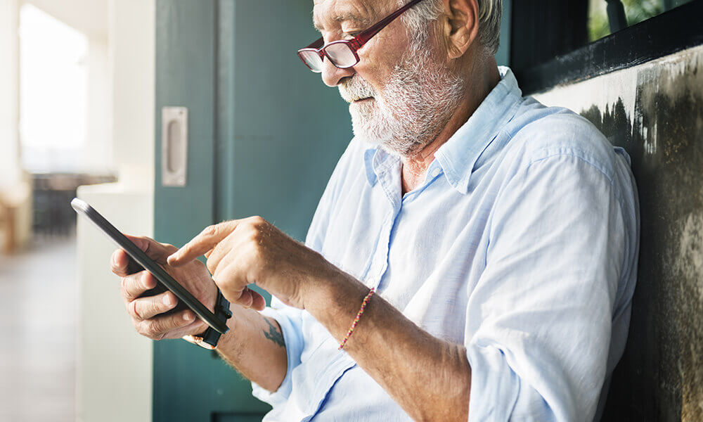 elderly man working on tablet