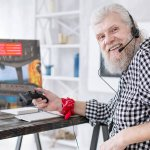 senior man playing video games at home
