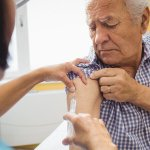 doctor injecting vaccine into senior patient
