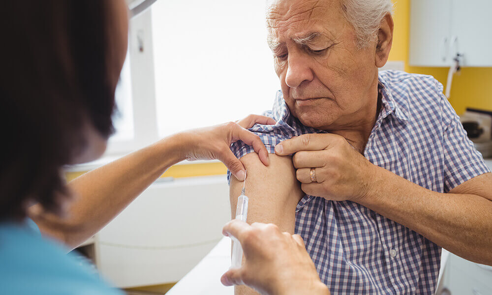 an elderly man getting his seasonal vaccinations