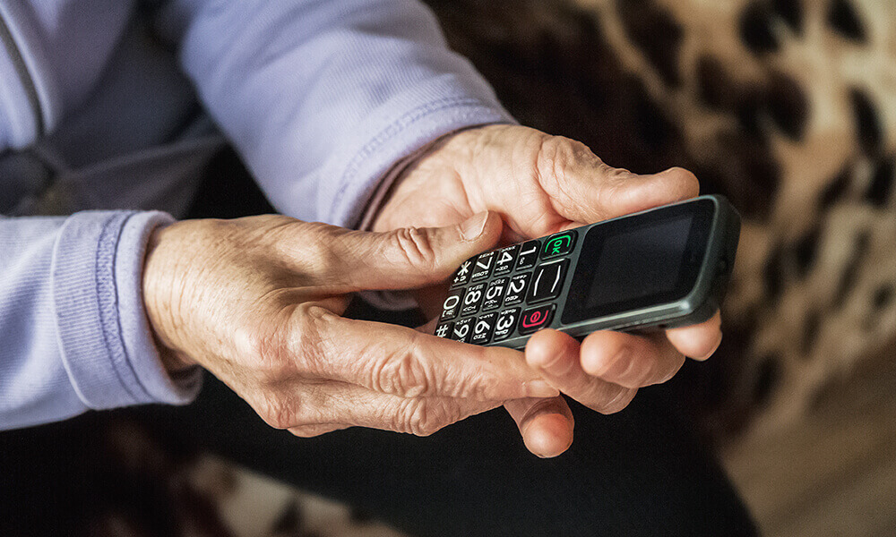 elderly hands holding smart phone technology
