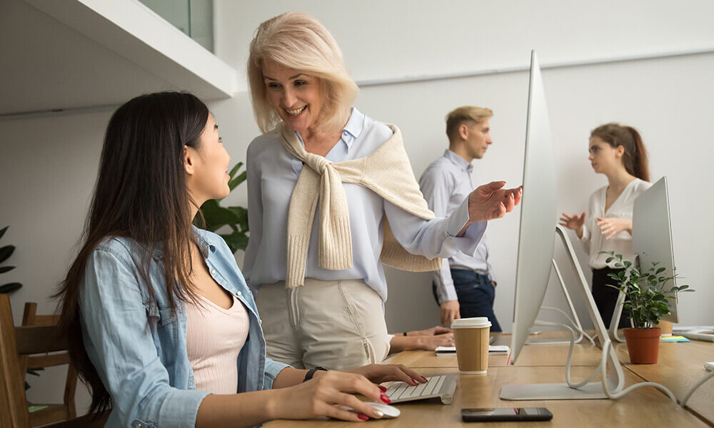two multi-generational women work together at an office