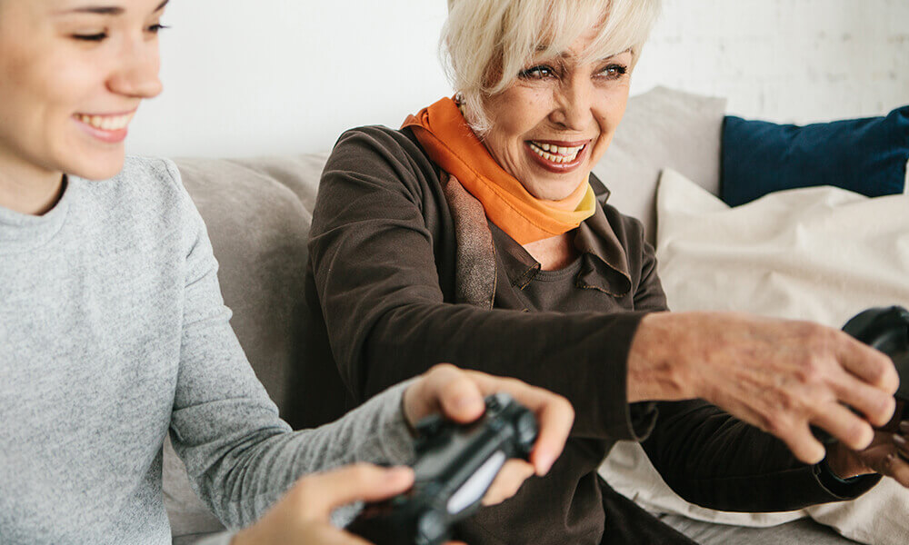 a senior woman and her grand-daughter gaming