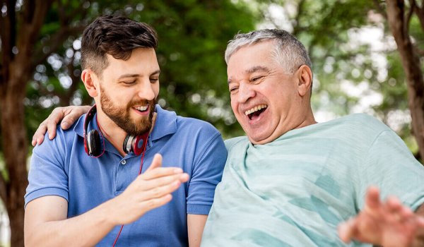 son and father laughing in a park