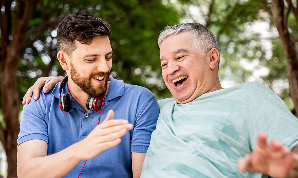 young male student laughing with senior living partner