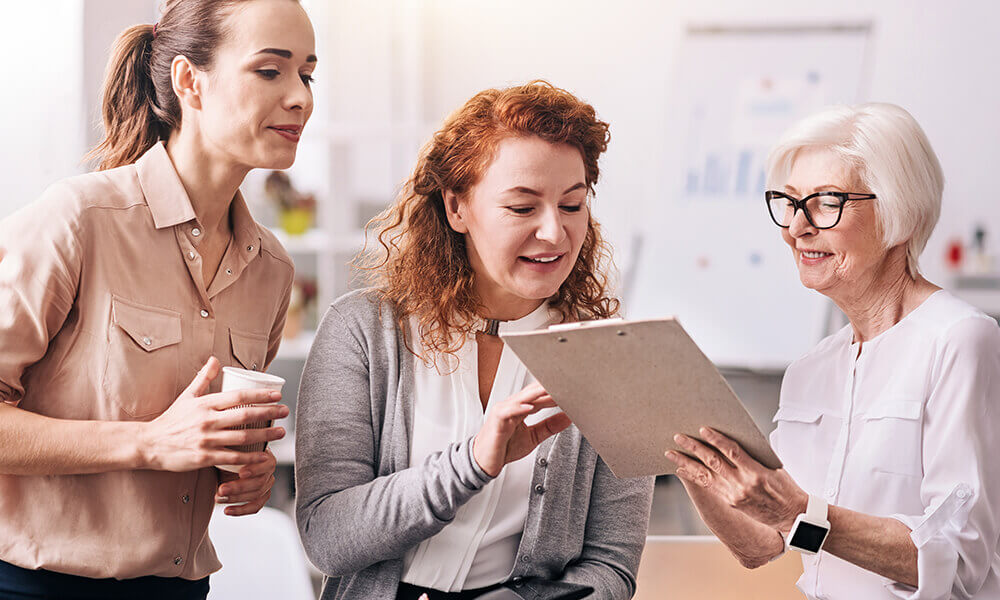 a group of multi-generational women work together in an office
