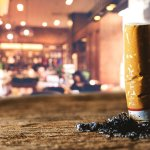 cigarette bud burning into a tabletop in a bar