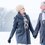 senior couple holding hands while on walk